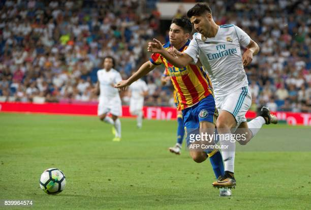 Valencia's midfielder Alvaro Medran vies with Real Madrid's midfielder Marco Asensio during the Spanish league football match Real Madrid CF vs...