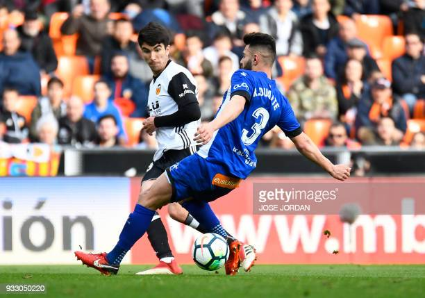 Valencia's midfielder Carlos Soler vies with Deportivo Alaves' defender Ruben Duarte during the Spanish League football match between Valencia CF and...