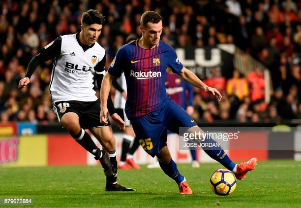 Valencia's midfielder Carlos Soler vies with Valencia's Barcelona's Dutch defender Thomas Vermaelen during the Spanish league football match Valencia...