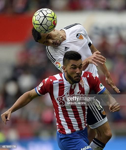 Valencia's midfielder Javi Fuego jumps for the ball with Sporting Gijon's forward Miguel Angel Guerrero Martin during the Spanish league football...
