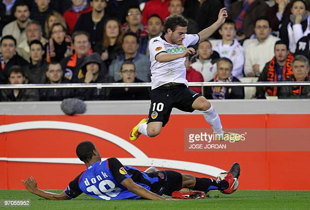 Valencia's midfielder Juan Mata vies for the ball with Brugge's Ryan Donk during their Europe league football match at Mestalla Stadium in Valencia...
