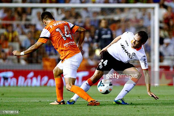 Valencia's midfielder Michel vies with Malaga's Chilean midfielder Pedro Morales during the Spanish league football match Valencia CF vs Malaga CF at...
