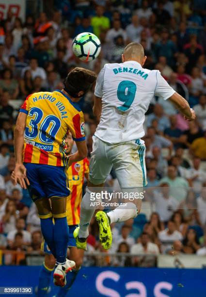 Valencia's midfielder Nacho Vidal jumps for the ball with Real Madrid's French forward Karim Benzema during the Spanish league football match Real...