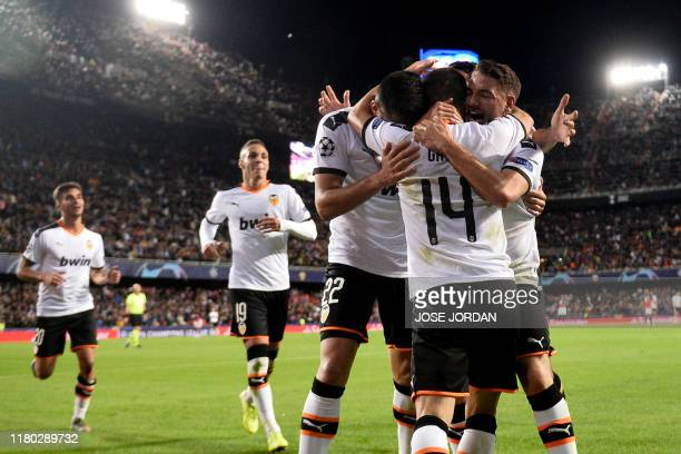 TOPSHOT Valencia's players celebrate after Lille's French defender Adama Soumaoro scored an own goal during the UEFA Champions League group H...