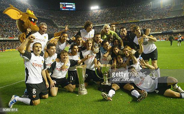 Valencia's players celebrate on their field in Valencia with their cups after winning the title Spanish soccer league 2004 and the UEFA Cup 23 May...
