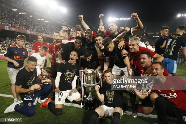 TOPSHOT Valencia's players celebrates with the trophy after winning the 2019 Spanish Copa del Rey final football match against Barcelona at the...