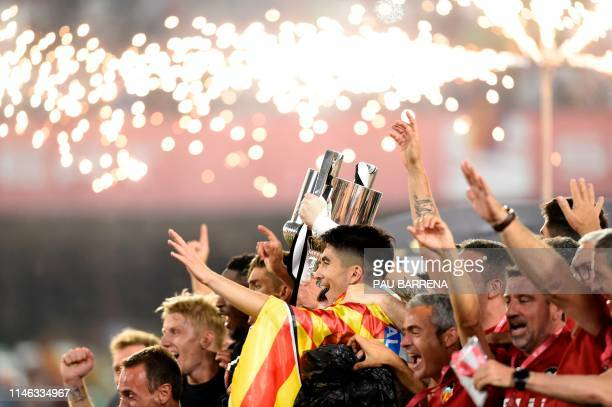 Valencia's players celebrates with the trophy after winning the 2019 Spanish Copa del Rey final football match against Barcelona at the Benito...