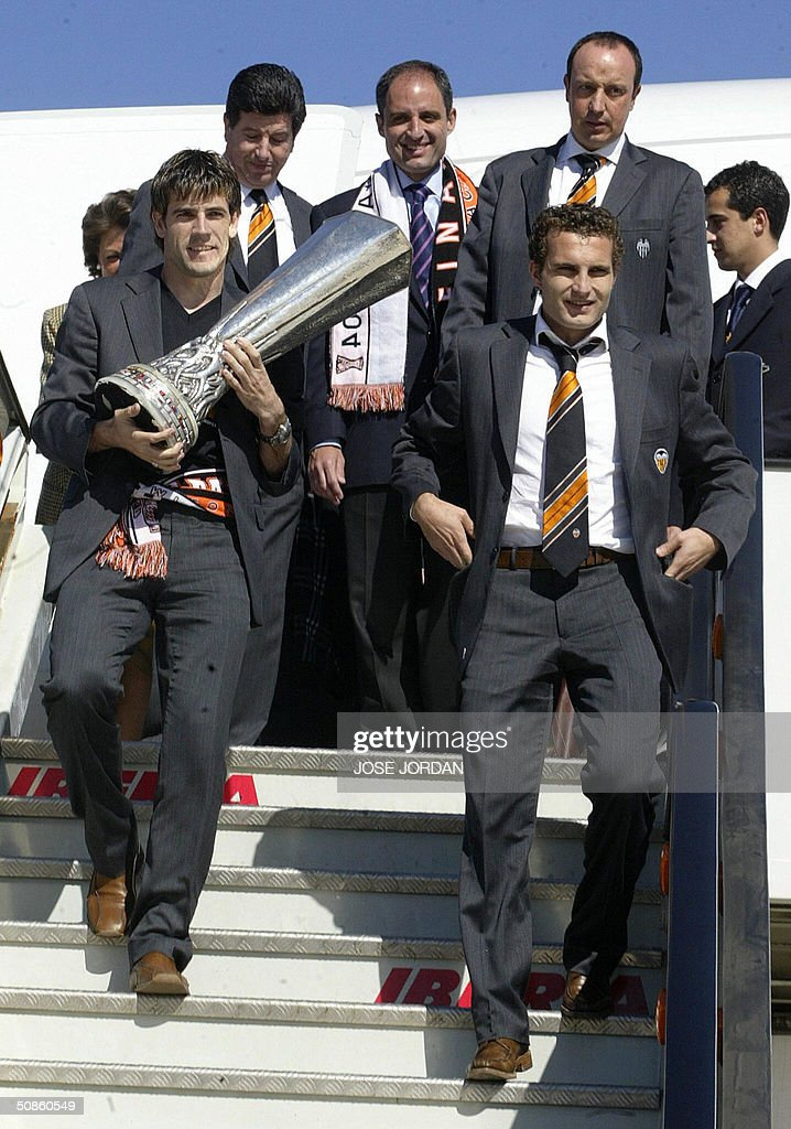 Valencia's players, David Albelda (L front) Ruben Baraja (R front) coach Rafa Benitez (R behind) Valencian country president Francisco Camps (C) and Valencia team president Jaime Orti (L behind) arrive at Valencia airport with the UEFA cup, 20 May 2004.