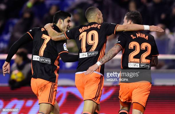 Valencia's Portuguese forward Goncalo Guedes celebrates a goal with Valencia's Spanish forward Rodrigo Moreno and Valencia's Spanish forward Santiago...