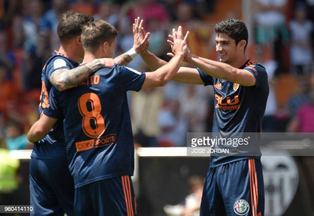 Valencia's Portuguese forward Goncalo Guedes celebrates a goal with Valencia's Spanish forward Santi Mina and Valencia's Argentinian forward Luciano...