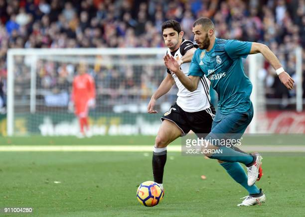 Valencia's Portuguese forward Goncalo Guedes vies with Real Madrid's French forward Karim Benzema during the Spanish league football match between...