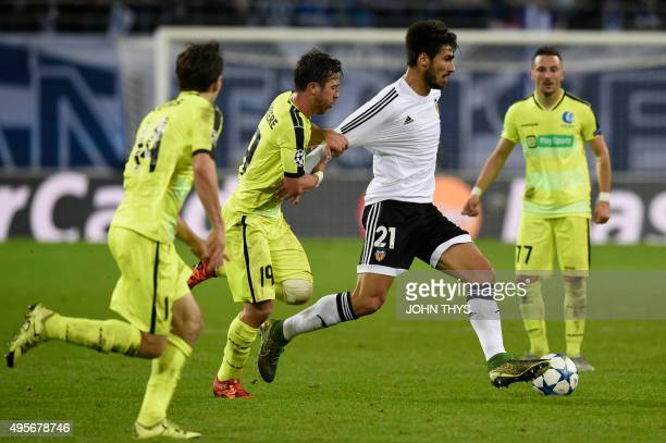 Valencia's Portuguese midfielder Andre Gomes vies for the ball with Ghent's Belgian midfielder Brecht Dejaeghere during the UEFA Champions League...