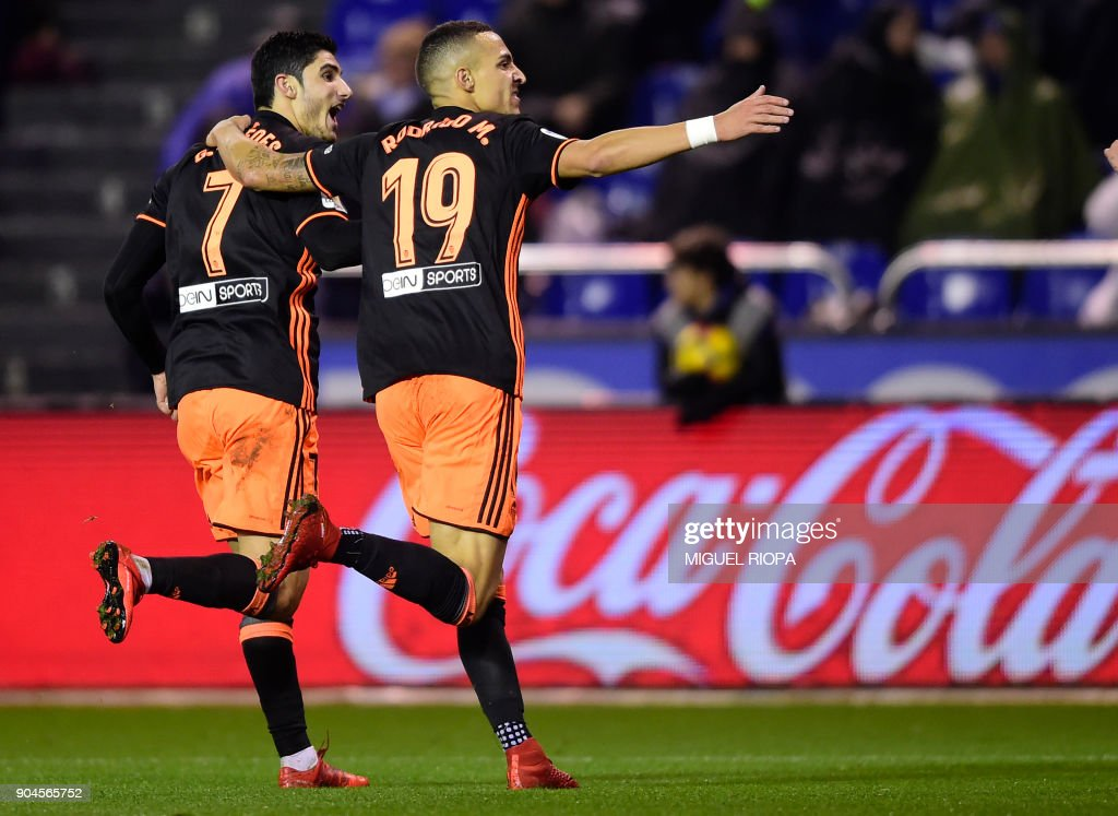 Valencia's Portuguese midfielder Goncalo Guedes (L) celebrates a goal with teammate Valencia's Spanish forward Rodrigo Moreno during the Spanish league football match between RC Deportivo de la Coruna and Valencia CF at the Municipal de Riazor stadium in La Coruna on January 13, 2018. /