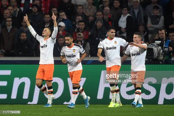 Valencia's Russian midfielder Denis Cheryshev celebrates with teammates after scoring a goal during the UEFA Champions League Group H football match...