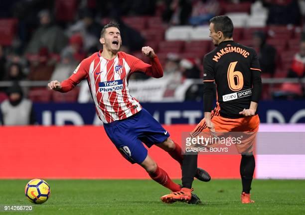 Valencia's Serbian midfielder Nemanja Maksimovic tackles Atletico Madrid's French defender Lucas Hernandez during the Spanish league football match...