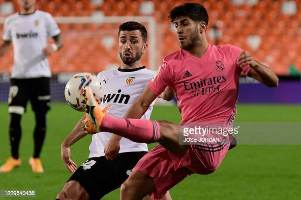 Valencia's Spanish defender Jose Luis Gaya Pena challenges Real Madrid's Spanish midfielder Marco Asensio during the Spanish League football match...