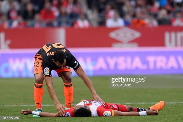 Valencia's Spanish defender Martin Montoya approaches Girona's Colombian defender Johan Mojica lying on the field during the Spanish league football...