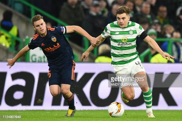 Valencia's Spanish defender Toni Lato challenges Celtic's Scottish midfielder James Forrest during the UEFA Europa League round of 32 first leg...