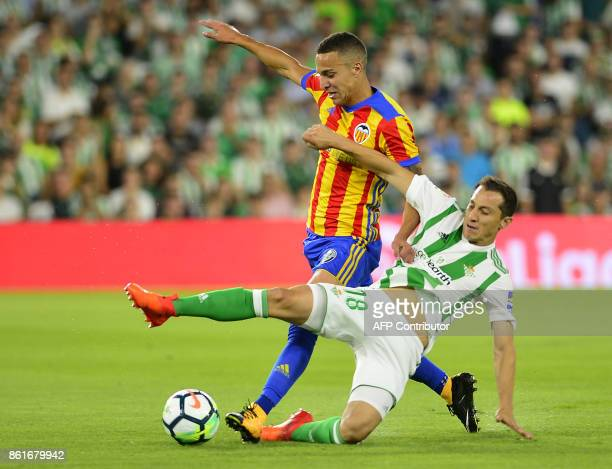 Valencia's Spanish forward Rodri fights for the ball with Real Betis' Mexican midfielder Andres Guardado during the Spanish league football match...