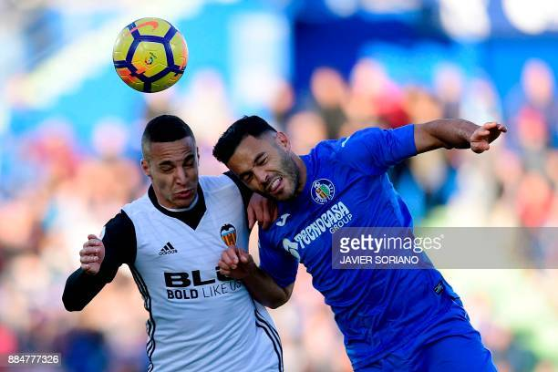Valencia's Spanish forward Rodri heads the ball with Getafe's Spanish defender Bruno Gonzalez during the Spanish league football match Getafe CF vs...
