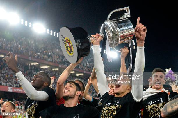 Valencia's Spanish forward Rodrigo Moreno holds the trophy as he celebrates with teammates after their team won the 2019 Spanish Copa del Rey final...