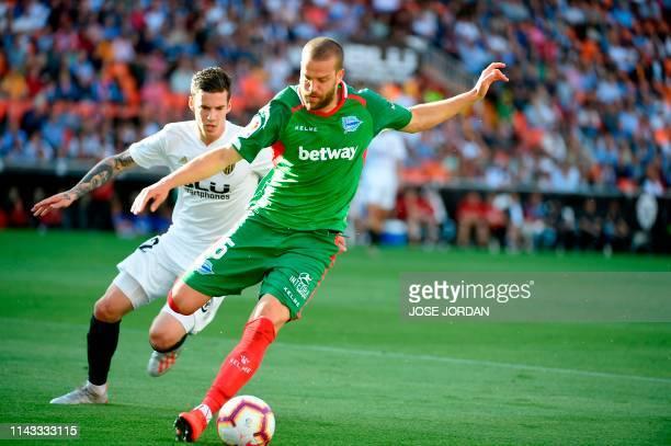 Valencia's Spanish forward Santi Mina challenges Alaves' Spanish defender Victor Laguardia during the Spanish League football match between Valencia...