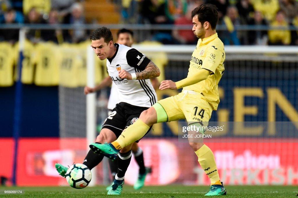 Valencia's Spanish forward Santi Mina (L) challenges Villarreal's Spanish midfielder Manu Trigueros during the Spanish league football match between Villarreal and Valencia at the La Ceramica stadium in Villarreal on May 5, 2018.