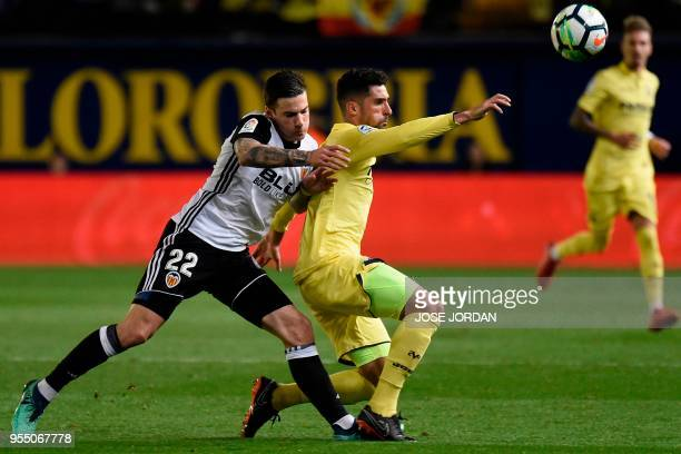 Valencia's Spanish forward Santi Mina challenges Villarreal's Spanish defender Alvaro Gonzalez during the Spanish league football match between...