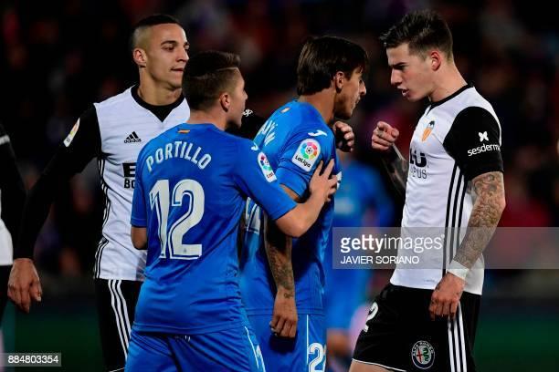 Valencia's Spanish forward Santi Mina Lorenzo and Getafe's Uruguayan defender Damian Suarez argue next to Valencia's Spanish forward Rodri and...
