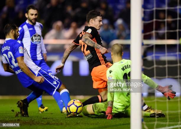 Valencia's Spanish forward Santi Mina vies with Deportivo La Coruna's Spanish goalkeeper Ruben Martinez during the Spanish league football match...