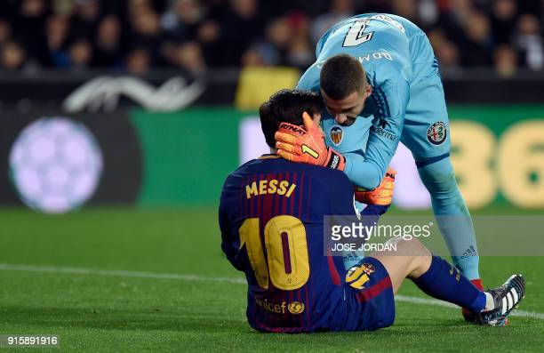 Valencia's Spanish goalkeeper Jaume helps Barcelona's Argentinian forward Lionel Messi to stand up after clashing during the Spanish 'Copa del Rey'...