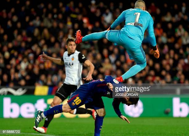 Valencia's Spanish goalkeeper Jaume jumps over Barcelona's Argentinian forward Lionel Messi during the Spanish 'Copa del Rey' second leg semifinal...
