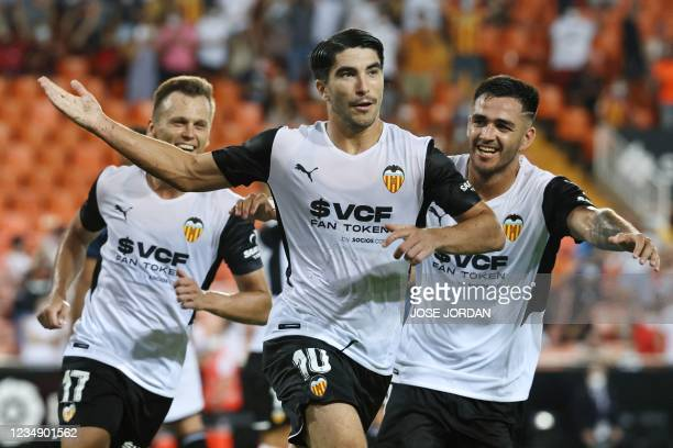 Valencia's Spanish midfielder Carlos Soler celebrates his team's second goal during the Spanish League football match between Valencia and Alaves at...
