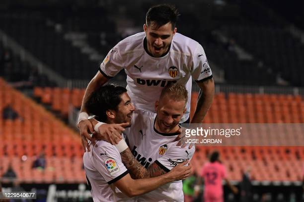 Valencia's Spanish midfielder Carlos Soler celebrates with Valencia's Uruguayan forward Maxi Gomez and Valencia's Serbian midfielder Uros Racic after...