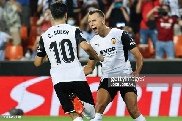 Valencia's Spanish midfielder Carlos Soler celebrates with Valencia's Russian midfielder Denis Cheryshev after scoring a goal during the Spanish...