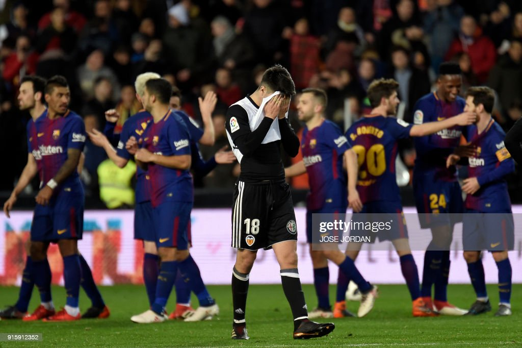 Valencia's Spanish midfielder Carlos Soler (C) covers his face as Barcelona players celebrate their qualification for the final match during the Spanish 'Copa del Rey' (King's cup) second leg semi-final football match between Valencia CF and FC Barcelona at the Mestalla stadium in Valencia on February 8, 2018. /
