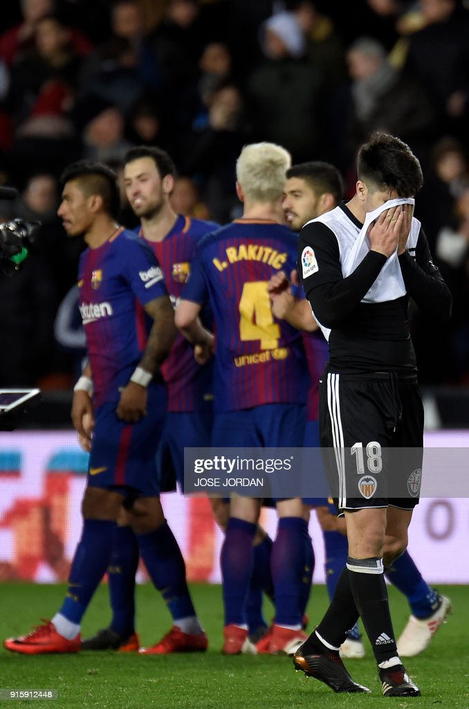 Valencia's Spanish midfielder Carlos Soler covers his face as Barcelona players celebrate their qualification for the final match during the Spanish 'Copa del Rey' (King's cup) second leg semi-final football match between Valencia CF and FC Barcelona at the Mestalla stadium in Valencia on February 8, 2018. /