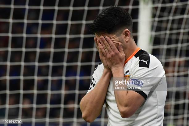 Valencia's Spanish midfielder Carlos Soler reacts after missing a goal opportunity during the UEFA Champions League round of 16 first leg football...