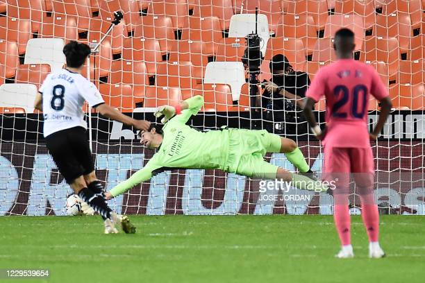 Valencia's Spanish midfielder Carlos Soler scores a penalty past Real Madrid's Belgian goalkeeper Thibaut Courtois during the Spanish League football...