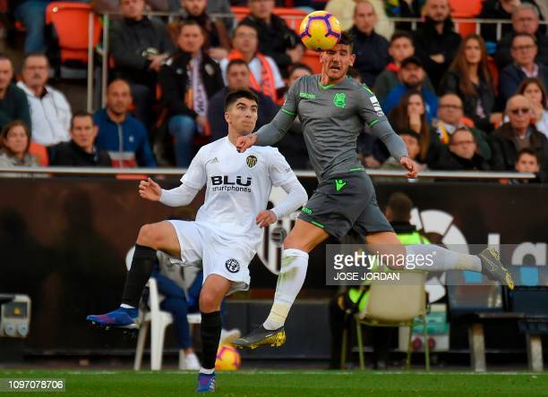 Valencia's Spanish midfielder Carlos Soler vies with Real Sociedad's French defender Theo Hernandez during the Spanish league football match Valencia...