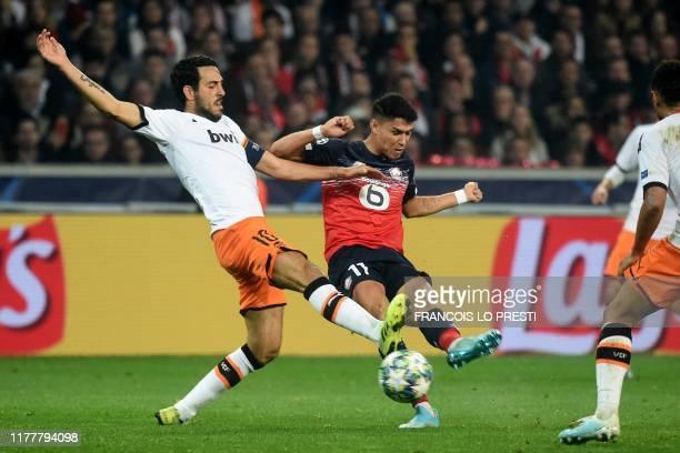 Valencia's Spanish midfielder Daniel Parejo and Lille's Brazilian forward Luiz Araujo vie for the ball during the UEFA Champions League Group H...