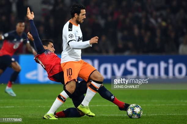 Valencia's Spanish midfielder Daniel Parejo and Lille's French midfileder Benjamin Andre vie for the ball during the UEFA Champions League Group H...