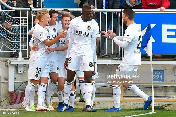 Valencia's Spanish midfielder Daniel Parejo celebrates with teammates after scoring a goal during the Spanish League football match between Deportivo...