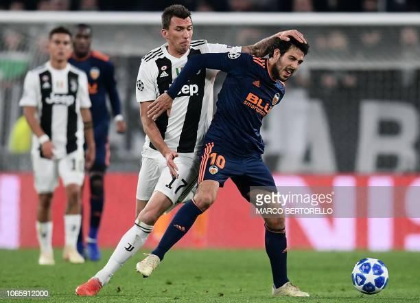 Valencia's Spanish midfielder Daniel Parejo holds off Juventus' Croatian forward Mario Mandzukic during the UEFA Champions League group H football...