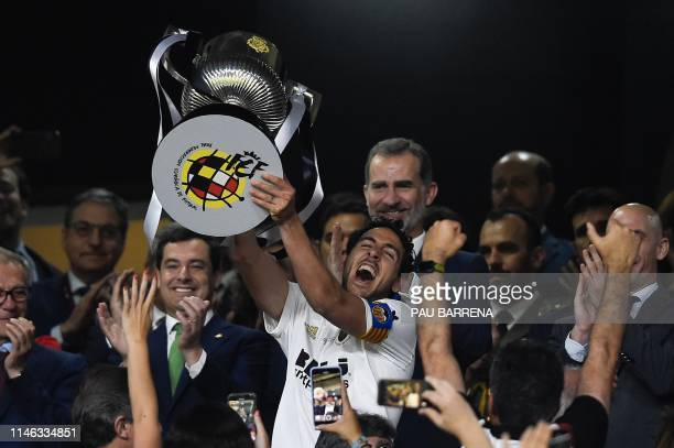 Valencia's Spanish midfielder Daniel Parejo holds the trophy in front of Spain´s King Felipe VI as he celebrates after winning the 2019 Spanish Copa...