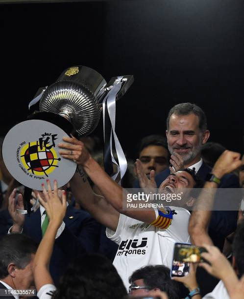 Valencia's Spanish midfielder Daniel Parejo holds up the trophy in front of Spain's King Felipe VI as he celebrates after winning the 2019 Spanish...