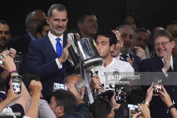 Valencia's Spanish midfielder Daniel Parejo kisses the trophy beside Spanish king Felipe VI after winning the 2019 Spanish Copa del Rey final...