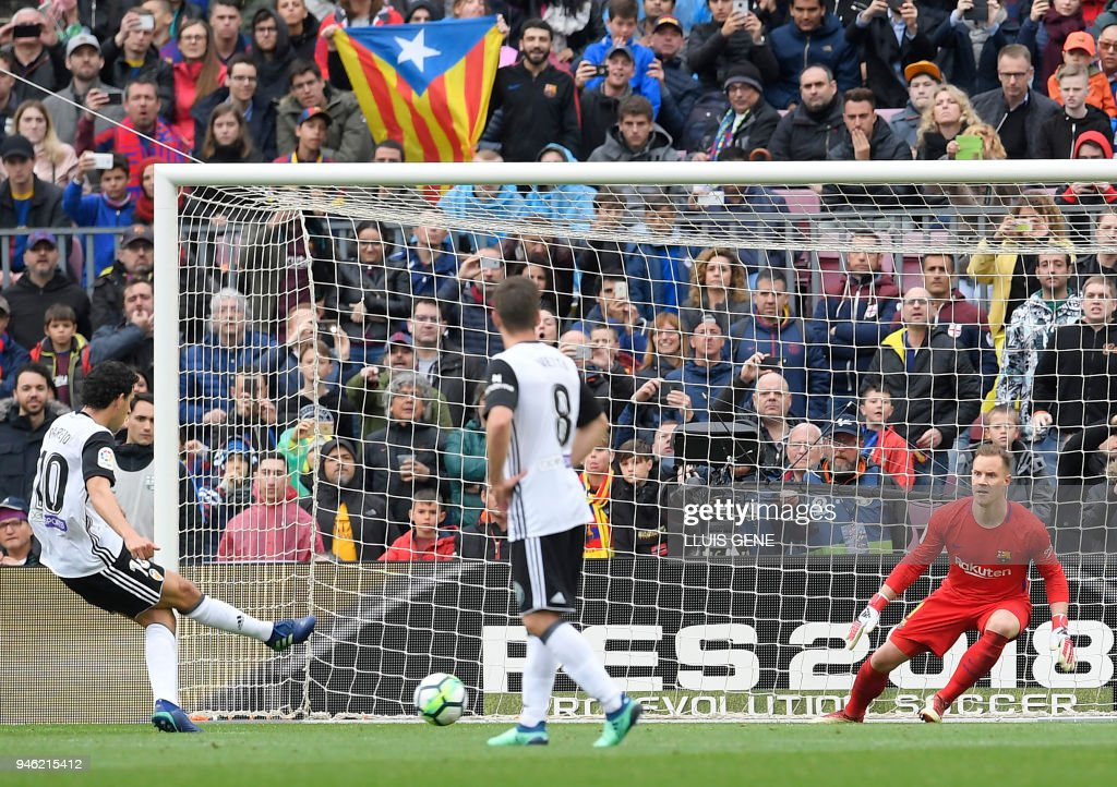 Valencia's Spanish midfielder Daniel Parejo (L) shoots a penalty kick to score a goal during the Spanish league footbal match between FC Barcelona and Valencia CF at the Camp Nou stadium in Barcelona on April 14, 2018. /