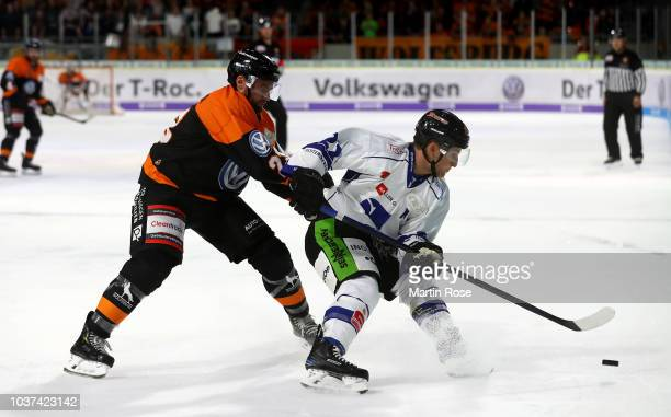 Valentin Busch of Wolfsburg and Mike Connolly of Straubing battle for the puck during the DEL match between Grizzlys Wolfsburg and Straubing Tigers...