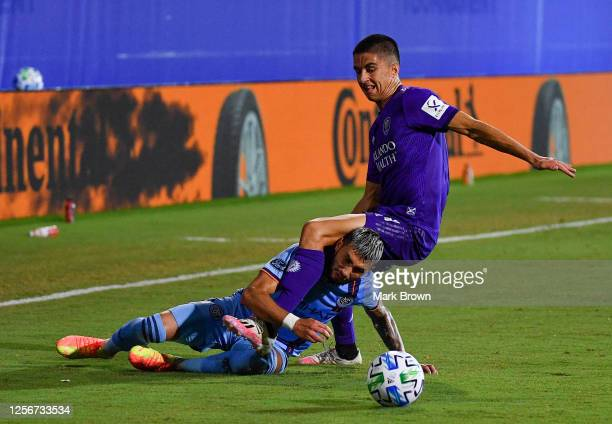 Valentin Castellanos of New York City FC slides tackles Joao Moutinho of Orlando City SC during a Group A match as part of MLS is Back Tournament at...